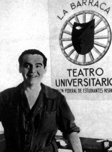 """Federico García Lorca con mono de mecánico y bajo el cartel de """"La Barraca""""."""