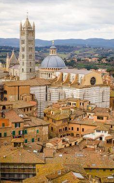 Tetti di #Siena: immagine aerea della città, coi suoi caratteristici edifici medievali. Si scorge la parte absidale della Cattedrale di Santa Maria Assunta, con il suo imponente Campanile. Seguici su Instagram: http://instagram.com/sunnytuscanytours