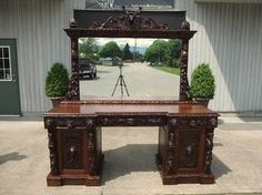 Georgian solid Oak Black Forest double pedestal sideboard or buffet. The large carved Deer head with antlers facing forward Beside are carved open mouth Griffins heads There are borders of crisply carved tongue and leaf throughout the piece. As well as carved nuts leaf & berries there are Maidens. The base is two pedestals joined by the large top all with raised panel sides and drawer fronts. The carved North Wind face drawer and door pulls are fantastic