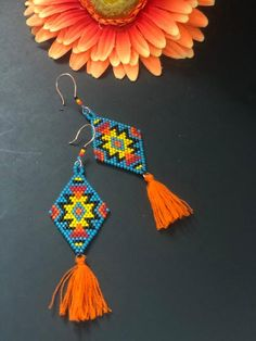 Hand beaded earrings made with lots of passion for color and geometric pattern. Woven with glass delica beads in turquoise, orange, yellow red and black. Finished with handmade tassels. Handmade copper-colored ear wires accented with beads. Long Tassel Earrings, Beaded Earrings, Beaded Jewelry, Beaded Bracelets, Diamond Jewelry, Flower Necklace, Handmade Copper, Handmade Jewelry, Leaf Pendant