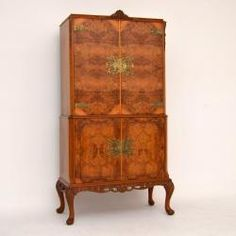 Fine quality walnut cocktail cabinet, with burr walnut doors, good carving & etched brass escutcheons. The front doors are a beautifully figured burr walnut, while the sides are figured walnut. All the corners are canted & it sits on solid walnut carved legs. The top interior of this cabinet is stunning & is lined in sycamore with a pull out mirrored slide for serving drinks on & many more features. It's antique Queen Anne style, probably made around the 1920-30's period & is in great…