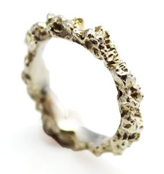 A handmade sterling silver ring with a thin band of organic texture that crevices and ripples around the finger.  £160