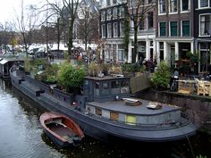 Houseboat, dutch barge with lots of foliage, makes the battleship grey not look so severe