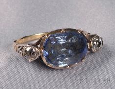 Antique Gem-set Ring, collet-set with a cushion-shape corundum with blue foil back, flanked by old mine-cut diamonds, silver and gold mount. [Something tells me this is at least 18th century, but I could be wrong. Foil backs and pinched collets give it away, however]