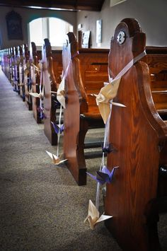 Beautiful cascading origami cranes on a ribbon ( instead of the usual church pew floral bouquet )