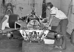 A rather tired looking McLaren mechanic and one of the later M23 Formula 1 cars. The McLaren mechanics were utilizing a very sophisticated stand to support the front of the car.