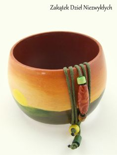 """Drewniana bransoleta z kolekcji """"Gdy słońce zachodzi"""" - o średnicy 7 cm i szerokości 5 cm, ręcznie malowana farbą akrylową w odcieniach zielonego, żółtego i pomarańczowego, zabezpieczona lakierem, zdobiona zielonym, bawełnianym sznurkiem oraz drewnianymi koralikami. Dzieło Wielkiego Słonia w Czerwone Paski."""