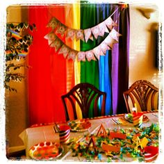 Rainbow Art Party- Decorations...table cloth backdrop ($ store), free printable banner, easels made from colored popsicle sticks ($ store), cups/plates/napkins/straws/crate paper/confetti/table cloth (Target) and paint chips folded (Home Depot- free).