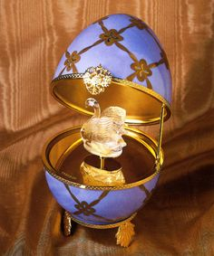 "This Faberge egg is made of hand painted Limoges porcelain and opens to reveal a Swan surprise that is made of hand-carved rock crystal. The elegant swan revolves as the Swiss-made musical movement plays Tchaikovsky's ""Swan Lake""."
