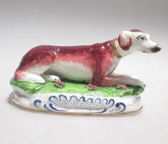 A Sherrat style porcelain figure of a reclining dog  - Cheffins