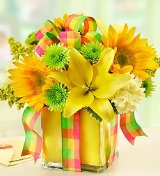All Wrapped Up - Yellow. EXCLUSIVE Let the sun shine in. Send a gift that brings instant smiles to their day with our radiant arrangement of brilliant yellow lilies, carnations and sunflowers. Gathered by hand in a chic cube vase, it's finished with a vibrant plaid ribbon and yellow foam liner, to deliver a smile that's wrapped and ready. The freshest yellow lilies, sunflowers and carnations, gathered with green poms, bright solidago and variegated pittosporum Hand-arranged in a stylish…