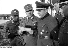 """Borislav Kaminski (3rd from left), Nazi collaborator and commander of a Russian regiment of pro-Nazi volunteers known as the """"Kaminski Brigade,"""" confers with German police officers on anti-partisan operations. Kaminski fell out of favor eventually and he was killed on August 28, 1944 under undetermined circumstances; one theory was that he was ambushed by partisans, another that he was arrested and shot by the Gestapo."""