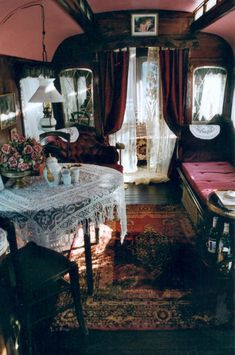 Small sitting room full of lace and burgundy, popular in Victorian period. Love the deep rose on the wall and in the bouquet of roses, and the paned windows.  Curved ceiling makes this look like a mobile home or train car?