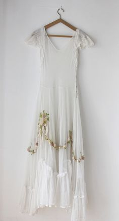 Wedding Dress: 1930's, white tulle, with tiers of embroidery made up of silk ribbon and wool flowers and bow motifs, in pale pinks, greens, apricot colours.