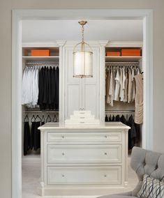 The gorgeous dressing island takes center stage in this well-appointed his and her master closet. Continuing the stone floor from the bathroom into the closet keeps things open and inviting. Marianne Jones LLC Marianne Jones - Birmingham, MI