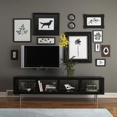 Camouflage the TV with Art      Here, a grouping of black and white silhouettes and prints of different shapes and sizes forms a collage on the wall with the television screen as its anchor