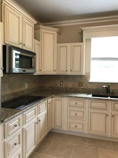 Creamy off white painted kitchen cabinets with brown glaze. Gorgeous granite and tumbled travertine tile backsplash. Color is Sherwin Williams Steamed Milk with General Finishes glaze. Check out these before and afters!