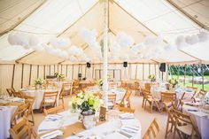 White pompoms decorating marquee ceiling   Photography by http://photography34.co.uk/