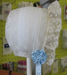 Horseshoe lace bonnets are a great way to put smaller lace pieces to good use. This is an old Simplicity pattern #6072. Blue silk satin rosettes and ties. Made by Trudy Horne.