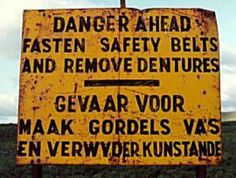Unusual road sign . . . .  Unusual weird Dutch translation. It says something like:   Danger for  Fasen seatbelts (in Dutch there has to be a t as well: vast)  and remove fake teeth (In Dutch it has to say: kunsttanden)