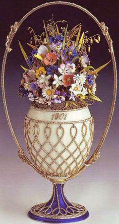 """1901 Uovo il cesto di fiori - Il Basket of Flowers Egg, conosciuto anche come """"Wild Flowers Egg"""", è fatto di argento, il vaso dorato, smalto guilloché opalescente color madreperla e blu scuro, diamanti taglio rosa, smalto verde opaco e smalti multicolori per i fiori. Lo zar Nicola II lo ha presentato a sua moglie, l'imperatrice Aleksandra Fyodorovna il 14 aprile 1901, giorno della Pasqua ortodossa."""