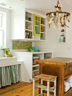 Built in shelves provide needed storage for this laundry room, while a farm sink, a one of a kind shell chandelier, and a rustic wood bureau punctuate this charming utilitarian space. (Photo: Richard Leo Johnson)