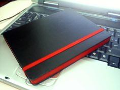 A Moleskine with a red accent. I love this black and red combination.