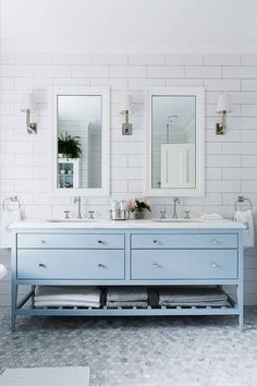 Gorgeous light blue and white bathroom remodel makeover with blue cabinets and white subway tiles with matching sconces and double his and hers sinks. So fresh and modern but classic and traditional at the same time!: