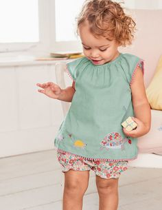 Choosing matching clothes in the morning is a breeze with this ready-made outfit. The play set's soft cotton fabric is given a special finish, with pompoms and animal appliqués. The elasticated neck of the short-sleeved top makes getting dressed easy – simply pull on those frilled bottoms and baby is ready to play.