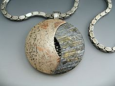 Betsy Baker creator of Stonehouse Studio. Semi hollow polymer clay pendant with vintage metal accents and chain.