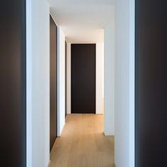 Nachthal met zwarte deuren van vloer tot plafond met ingebouwde grepen zodat er geen uitstekende elementen op de deur zitten.