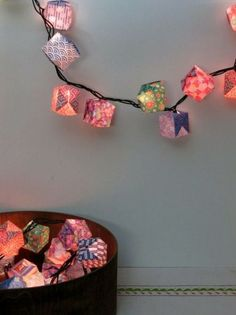 DIY, CRAFT, ORIGAMI LIGHTS    Turn left-over holiday lights into festive party lights, or into decorative and dim lighting for any room in the house! The origami cubes fit over the bulbs on the string of lights.USE SCRABOOK PAPERS FOR NEAT COLORS OR PATTERNS. Or create cool and calm lighting with paper straight from your printer......I am so doing this after Christmas !!!