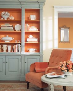 The dove gray of a bookcase tames the vibrant orange shelves and interior; the armchair's dusty-orange velvet upholstery is toned down by a cream-and-pale-green side table. It's easy to add orange shades with a flower arrangement like this clutch of coral roses.