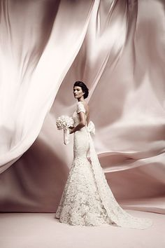Ines Di Santo - LISSOME  Ivory Alencon lace fit-to-flare gown with cameo pink underlay featuring a bateau neckline off-the-shoulder sleeve and dramatic lace bow at back