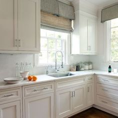 white cabinetry, tiles, moulding, wood floors, bottom mounted sink.  LOVE the window treatments - soften the room and definitely remind me of mom.