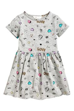 Short-sleeved dress in light, printed sweatshirt fabric with a gathered seam at the waist, bell-shaped skirt and sewn-in turn-ups on the sleeves. Lightly br