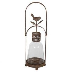 """Glass candle lantern with distressed floral ironwork.   Product: Candle lanternConstruction Material: Iron and glassColor: Rust and clearFeatures: Distressed finishAccommodates: (1) Candle - not includedDimensions: 14.5"""" H x 5.5"""" Diameter"""