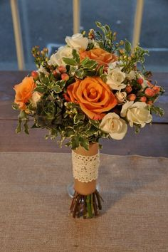 Rustic Charm Bridal Bouquet  A beautiful bouquet to match your rustic-style wedding.  This delicate pastel-hued bouquet consists of orange roses, ivory spray roses, succulents, peach hypericum berries, white waxflower  and variagated mini pittosporum leaves.  This bouquet is beautifully complimented by the burlap and lace wrap and pearl pins.  Finished with your choice of double-faced satin ribbon or burlap and lace and pearl or crystal pins. For more pictures and pricing visit our website