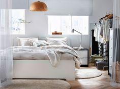 Vaalea makuuhuone, jossa valkoinen sänky, beiget vuodevaatteet ja korkeanukkaiset, luonnonvalkoiset matot.