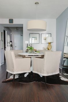 small beautiful dining room ....love the slipcovered chairs, large leaning mirror, cowhide rug and overhead pendant drum light.
