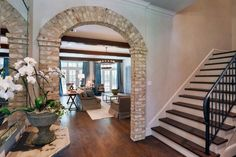 Southern-style brick arches frame the entry to the family room from the entry. Exposed wooden beams are another distinct Southern detail and are used throughout the home.