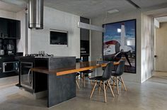 Contemporary Loft Finds The Perfect Balance Between Cool And Elegant A kitchen island with a wooden extension serves as a dining area. The rest of the kitchen is a black and white combo with a sleek and contemporary design.