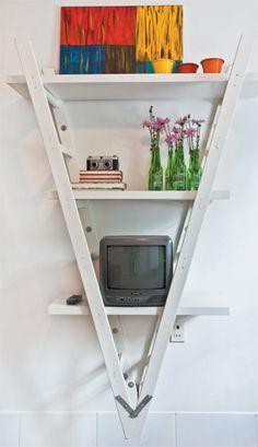"""A base da estante é uma escada de obra, colocada de forma invertida e pintada com esmalte sintético branco. """"Só acrescentamos prateleiras"""", afirma a arquiteta."""