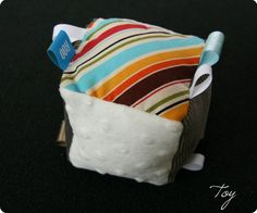 Great fabric scrap project: cloth baby block, with tags, texture, and crinkly noise thingy inside.