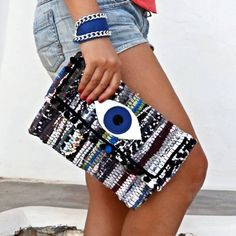 """Whimsical and fun, this kilim clutch decorated with the evil eye and colorful pom poms is sure to attract attention. Decorated with colorful pom poms its a statement piece that will carry your essentials in style. Pair it with a simple tee or your favorite maxi dress for easy going boho flair. Each bag is made of a kourelou a small rug made of recycled strips of cotton jersey fabrics. This makes every piece unique as no two bags are completely identical.  Size: 11""""x8,5"""", flap 4""""/28x21cm,..."""