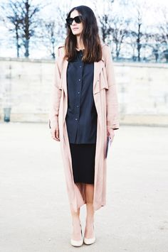 A long pale-pink trench coat is worn with a black button-down shirt, a black pencil skirt, black sunglasses, and nude pumps