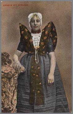 Vrouw in Axelse streekdracht. De vrouw draagt over de ondermuts en het oorijzer een 'trekmuts'. Ze draagt 'dubbele strikken' (dubbele, klaverbladvormige gouden oorijzerhangers) aan de 'krullen' (oorijzeruiteinden) van het oorijzer. Tussen de 'krullen' zijn twee gouden mutsenspelden in de muts gestoken. 1905-1911 #Axel