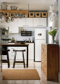 small kitchen ideas: baskets on top of cabinets; narrow table w/ bar stools; narrow standing cabinet thing with shelves above it. Wait, wont the pots hit you in the head? Small Kitchen Solutions, Small Kitchen Storage, Small Space Solutions, Extra Storage, Kitchen Small, Smart Storage, Creative Storage, Space Kitchen, Compact Kitchen