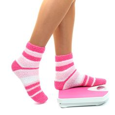 Woman's feet on scales in pink socks