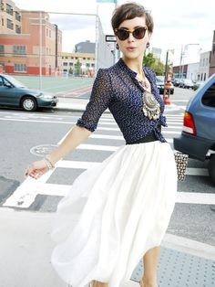 Pixie cut, navy pattern blouse, flowing white skirt, cat-eye sunglasses, large medallion necklace and leaf pattern clutch | The Glamourai